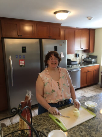 A woman smiles and chops food at a Thrive residence