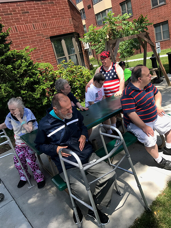 A group of people sitting outside of a Thrive residence