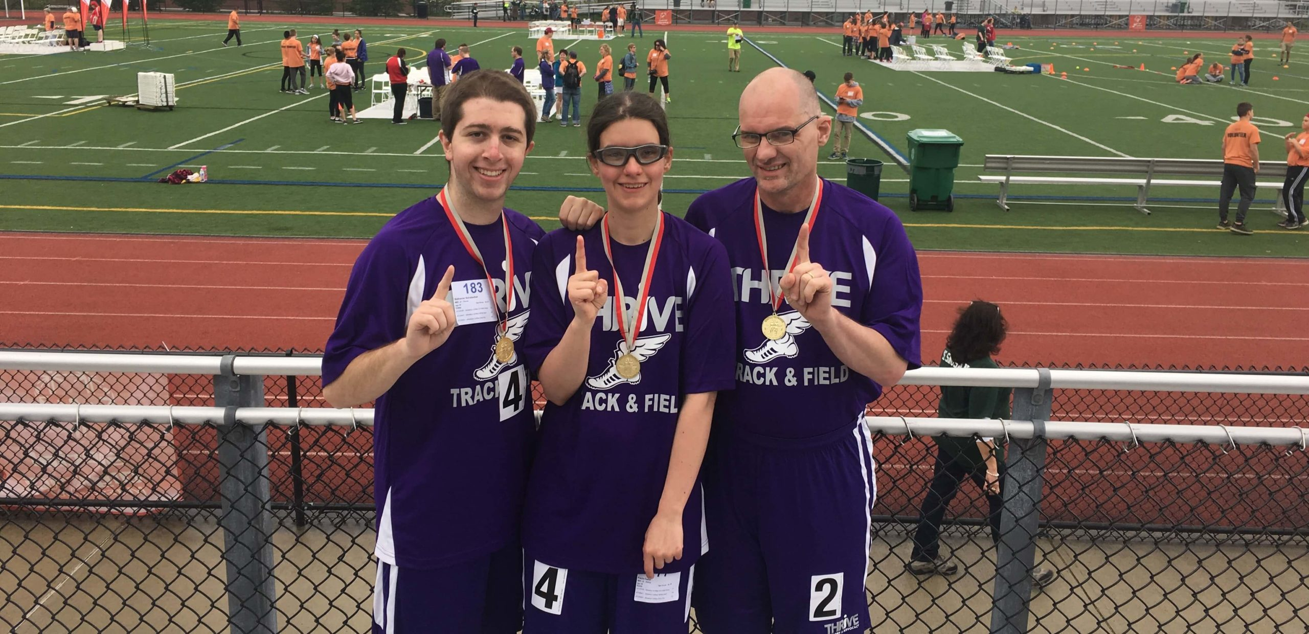 3 Special Olympics athletes pose with their medals
