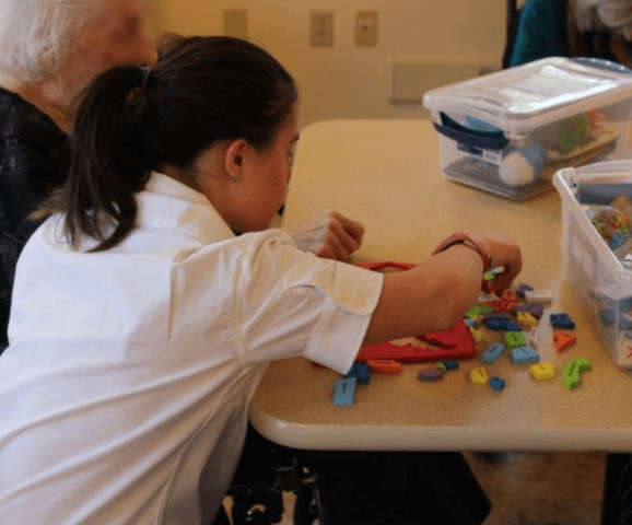 Thrive participant doing blocks with elderly person at nursing home